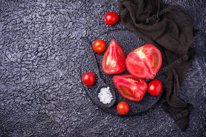 Sliced tomatoes on black background