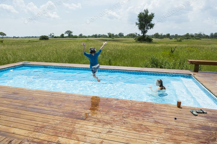 6 year old boy jumping into pool, tented camp, Botswana