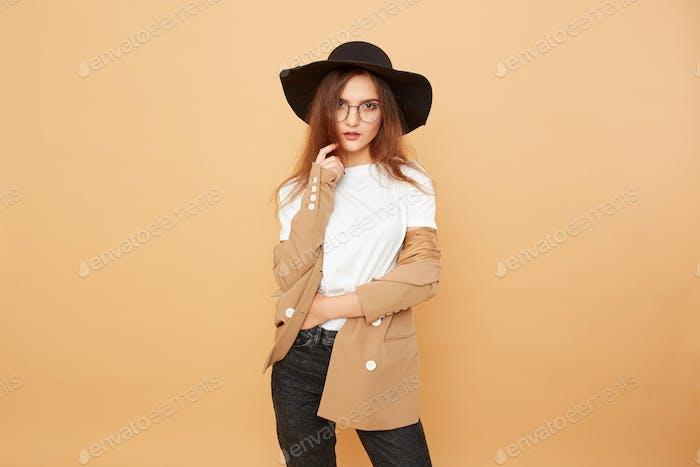 Стильная брюнетка девушка с длинными волосами в очках и черной шляпой на голове, одетой в белую футболку