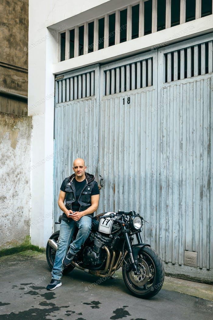 Байкер позирует с мотоциклом