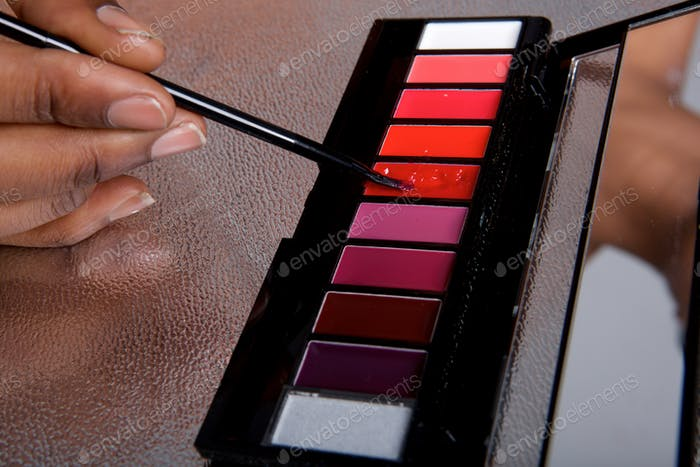 Close up lip gloss color palette and woman holding makeup brush