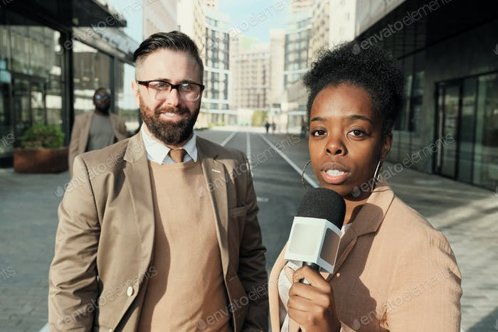 Reporter with businessman outdoors