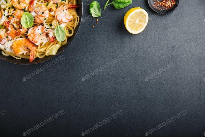Gebratene frische Garnelen mit Gewürzen auf schwarzer Pfanne