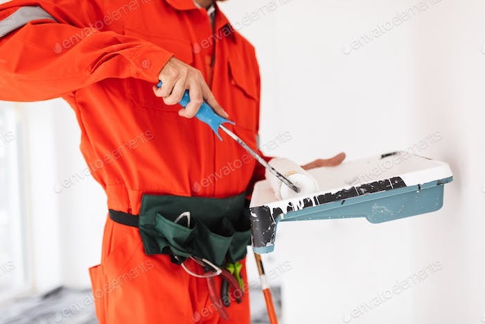 Close up foreman in orange work clothes using painting roller wi