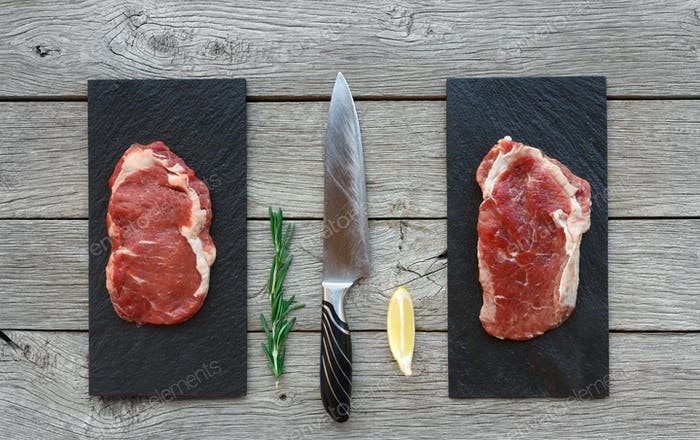 Raw beef steaks on dark wooden table background, top view