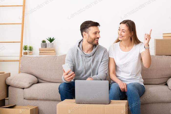 Young couple sitting in a new apartment and use laptop