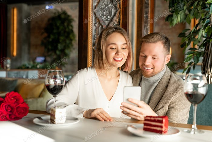 Young couple watching something in smartphone while sitting by served table