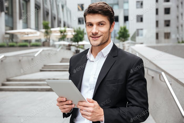 Attractive young businessman using tablet near business center