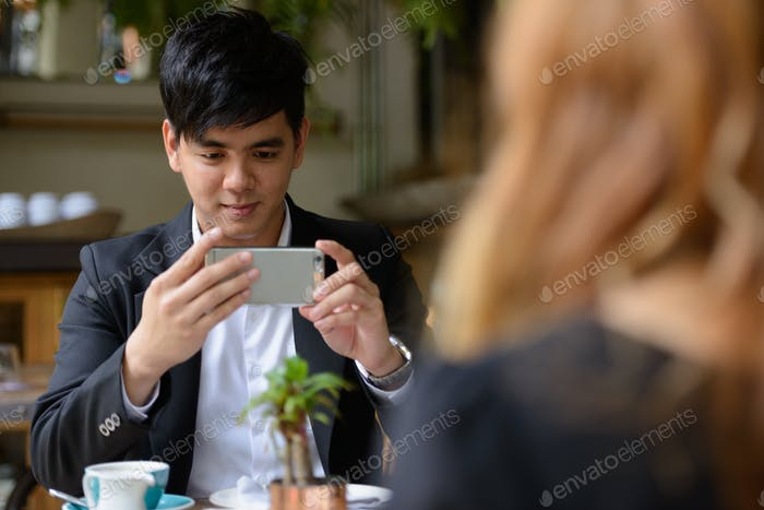Young Asian business couple together at the coffee shop with man taking picture using phone