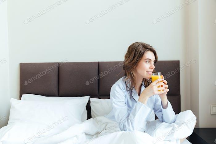 Portrait of a beautiful woman drinking orange juice in bedroom