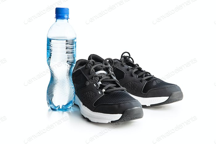 Black sports shoes and bottle of water