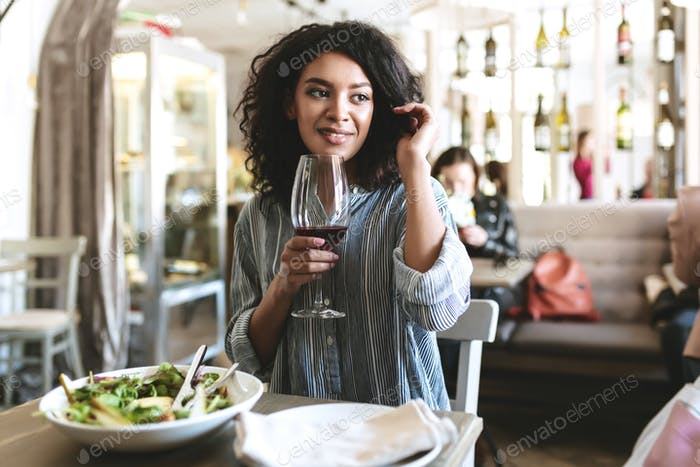African American girl sitting in restaurant with glass of red wine in hand and salad on table