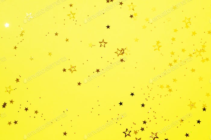 Golden star sparkles on yellow background. Christmas and New year concept. Festive backdrop with