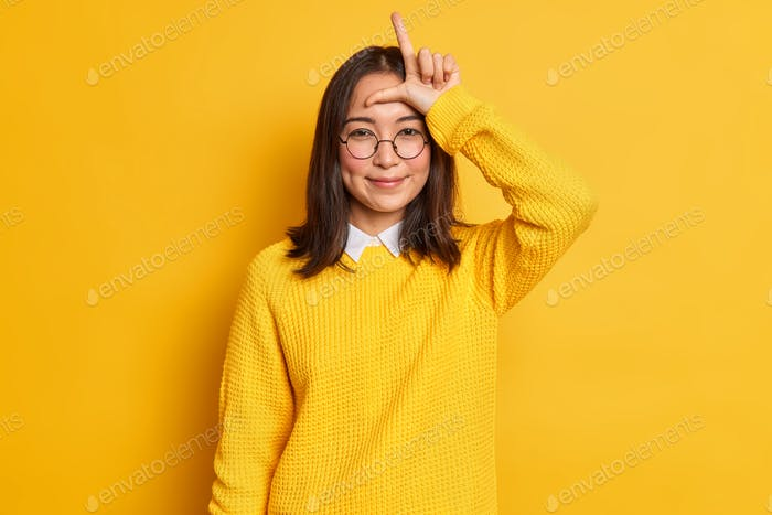 Indoor shot of smiling Asian girl makes loser gesture over forehead looks with satisfaction says fri