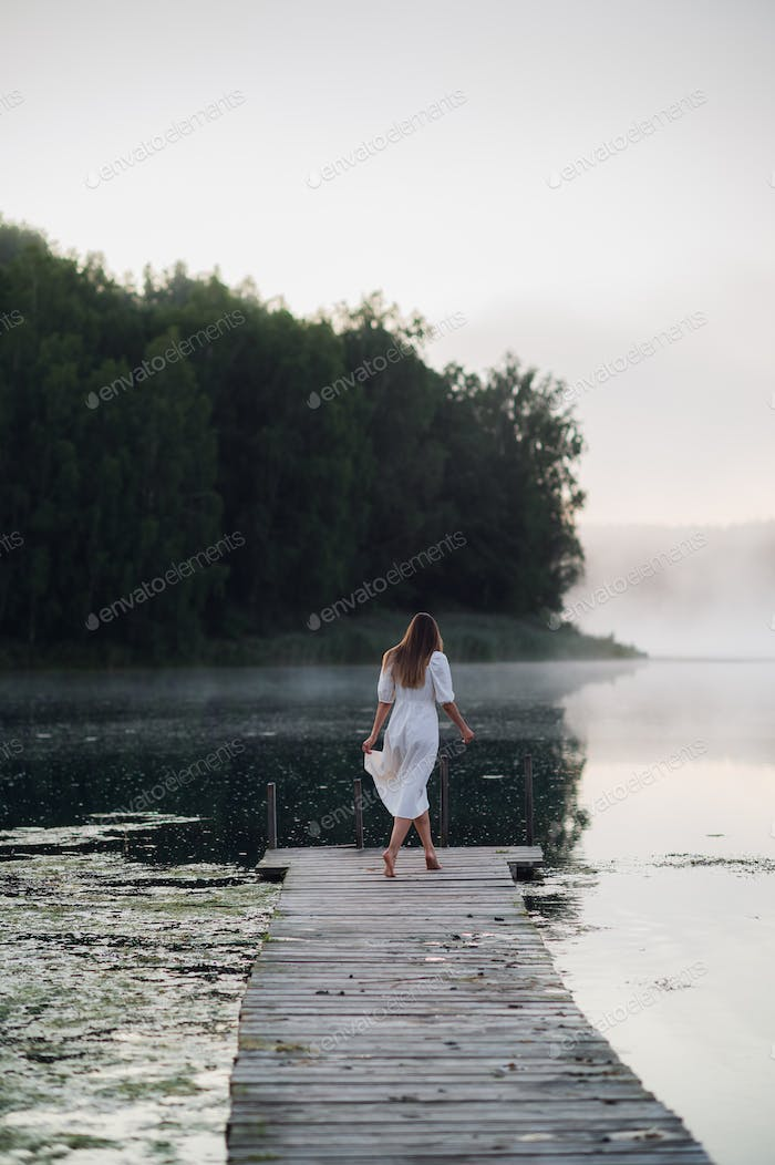 Young woman in white dress on a lake at chilly morning with a mist over water