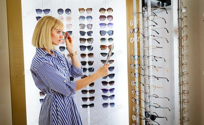 Gesundheits-, Seh- und Sehkonzept. Glückliche Frau Wahl Brille bei Optics Store