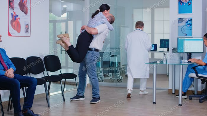 Husband hugging wife after receiving good news