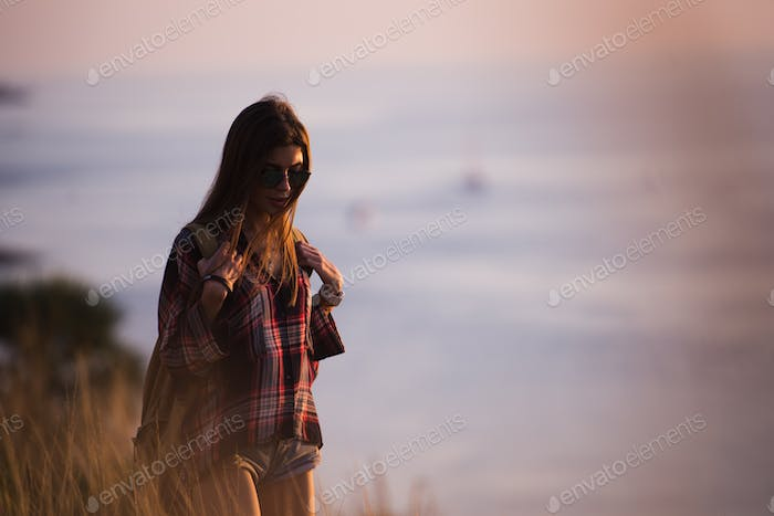 Summer sunny lifestyle fashion portrait of young stylish hipster woman walking in mountains, wearing