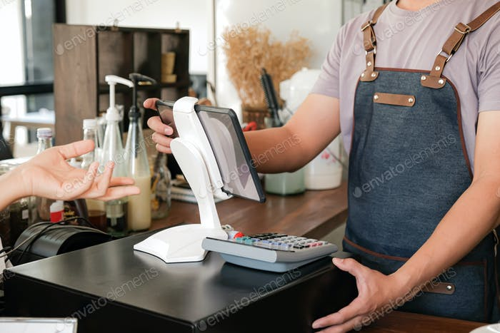 Barista is using the screen to receive orders from customers.