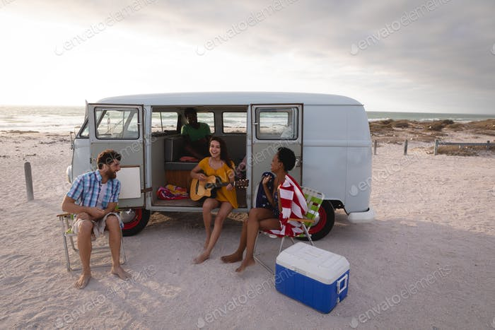 Friends enjoying at beach while standing near camper van on sunny day