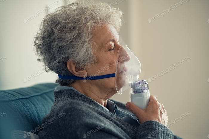 Sick senior woman making inhalation with nebulizer
