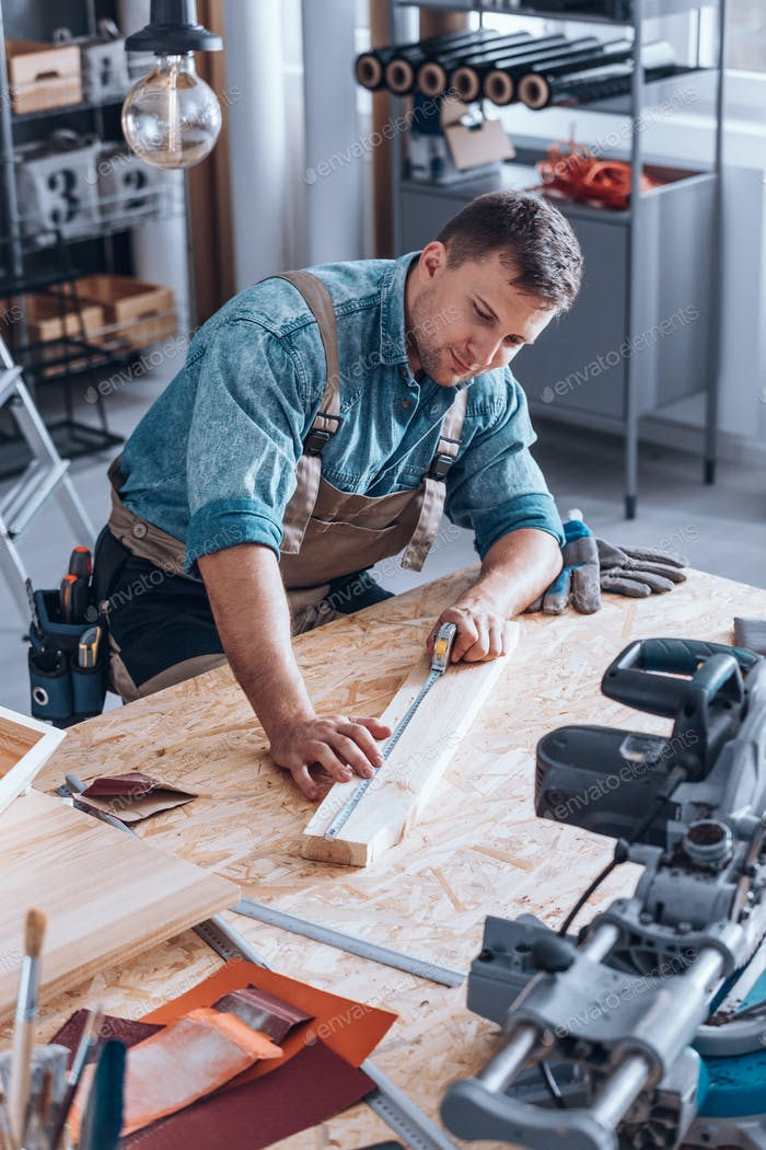 Modern carpenter measuring wooden plank