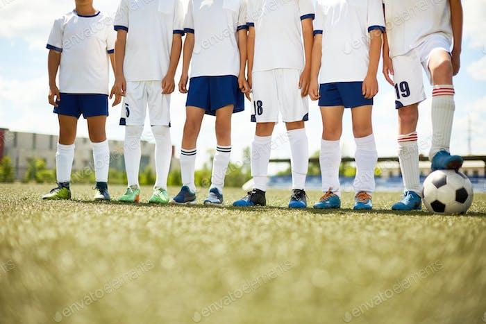 Unrecognizable Football Team in Field