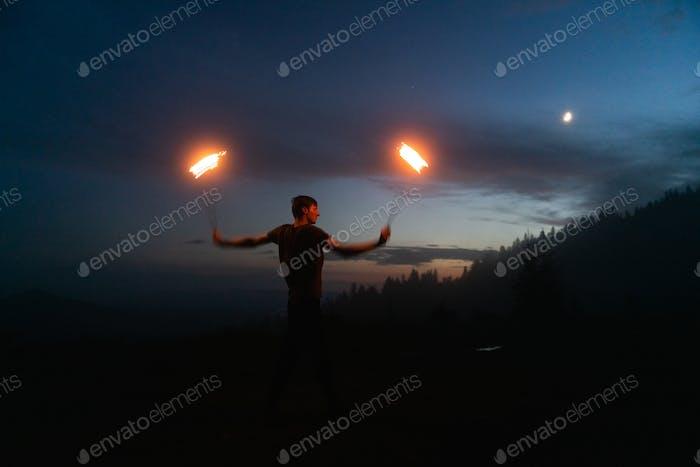 Graceful male fireshow performer making fire dance