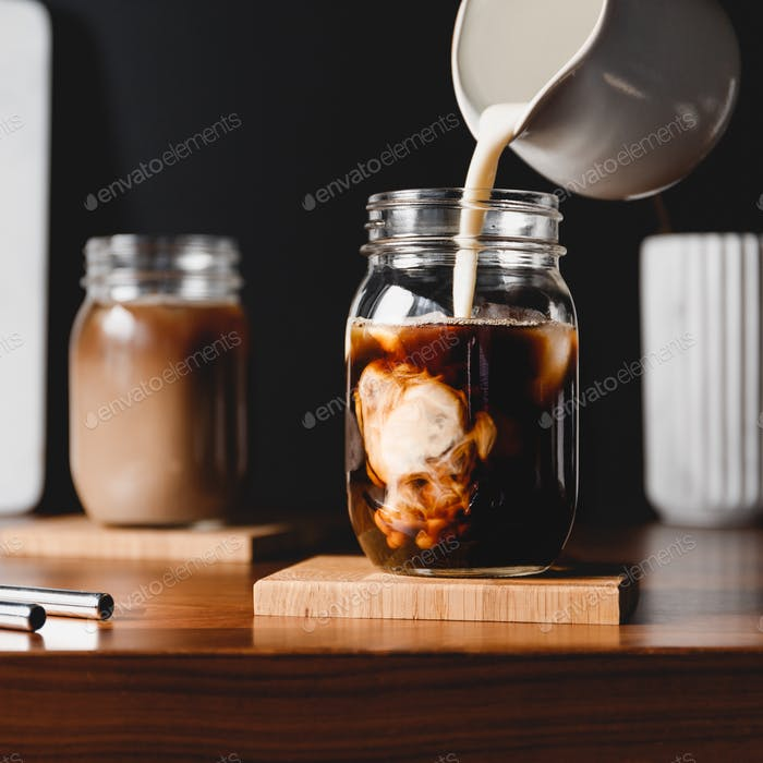 Making iced latte. Pouring vegetarian soy milk into a glass jar with black coffee and ice cubes.