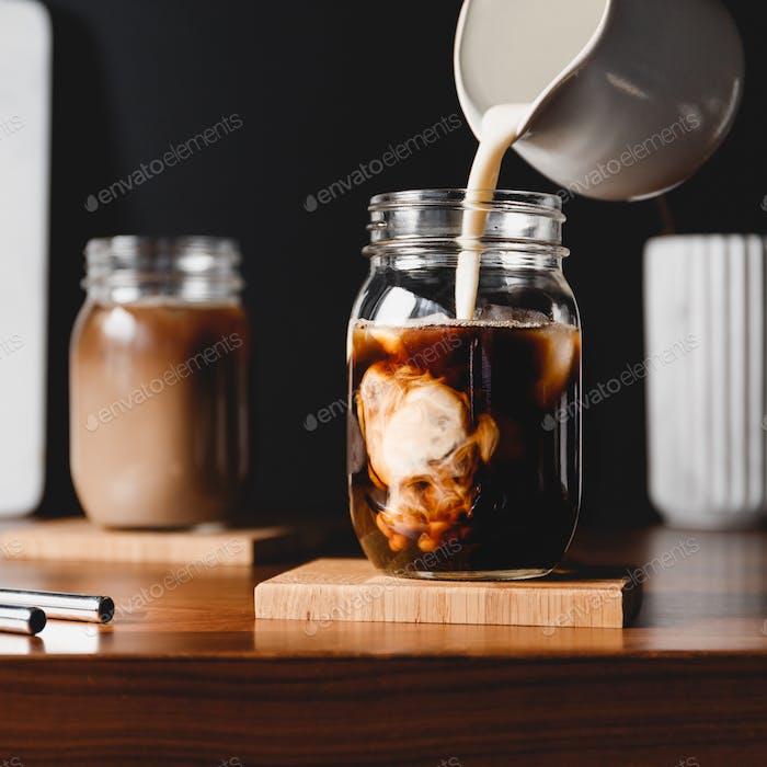 Herstellung von Eislatte. Vegetarische Sojamilch in ein Glas mit schwarzem Kaffee und Eiswürfeln gießen.