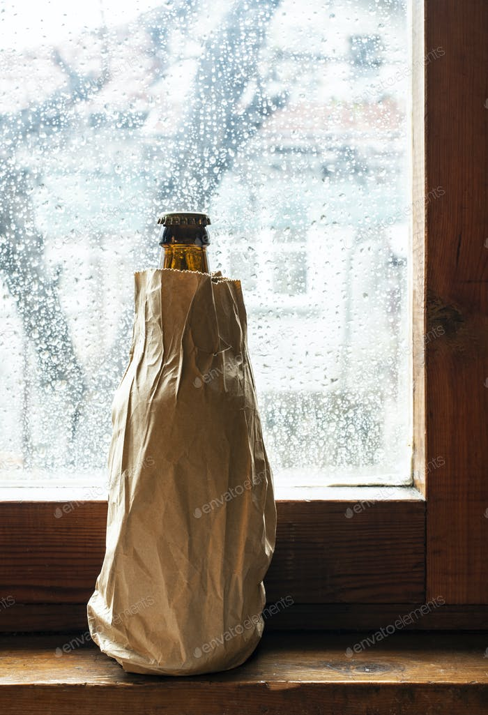 Bottle with alcohol in a brown pack paper placed to the window a