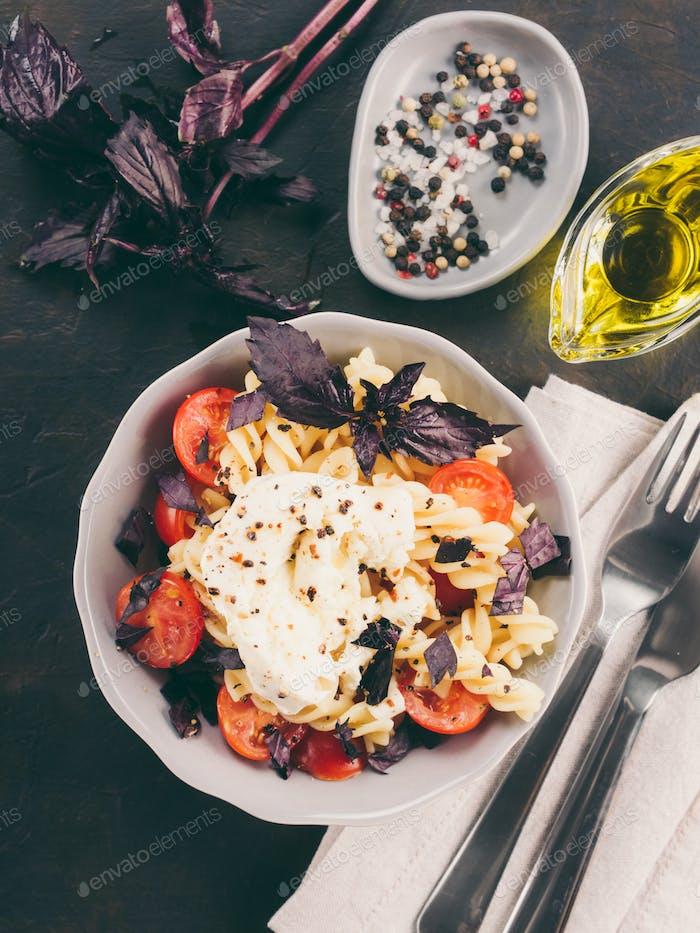 Pasta fusilli with cherry, mozarella and basil
