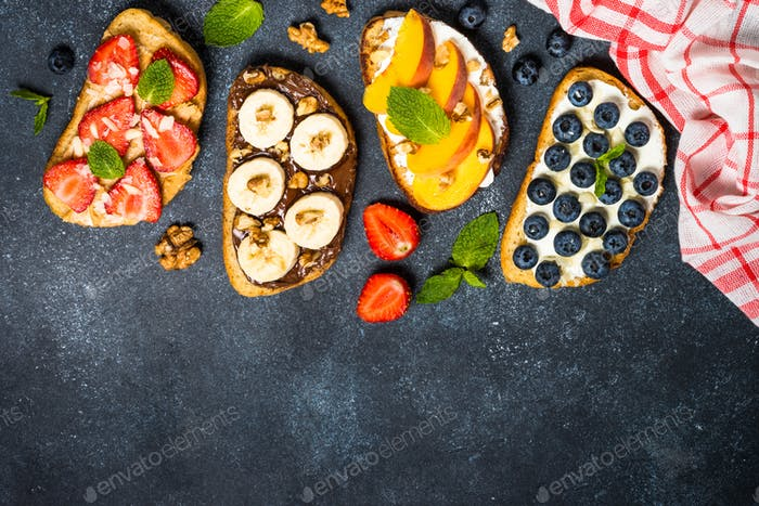 Sweet toast assortment with fresh fruit and berries on black