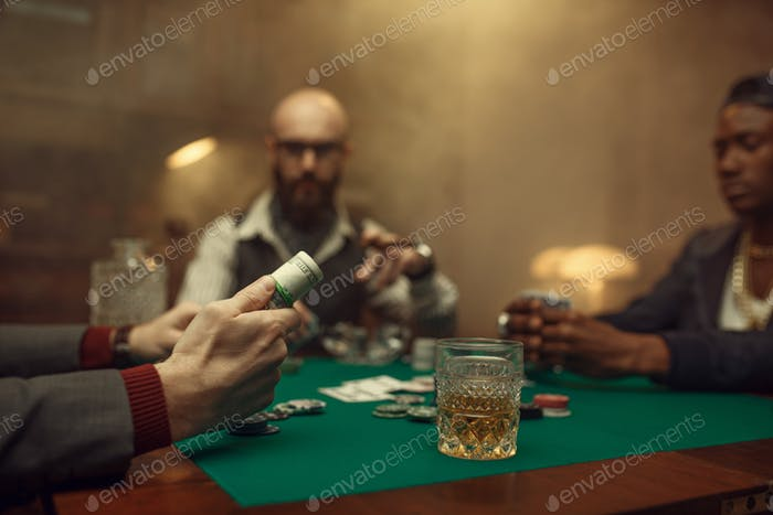 Poker player holds roll of money, casino