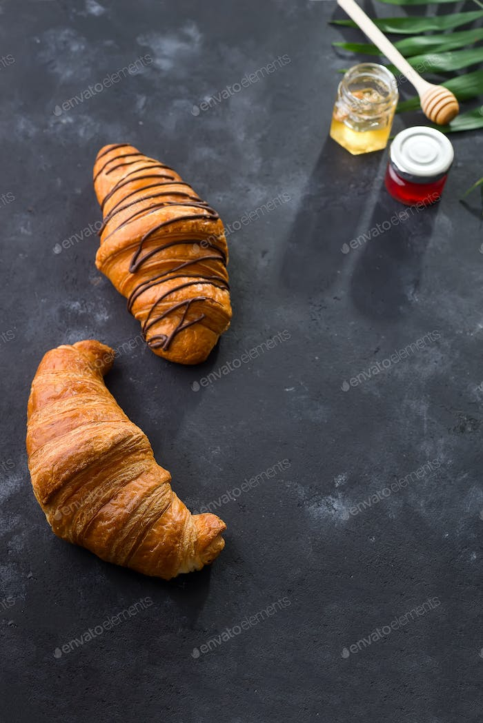 freshly baked croissant decorated with chocolate sauce, jar with jams and palm leave
