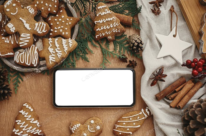 Phone with empty screen and festive gingerbread cookies