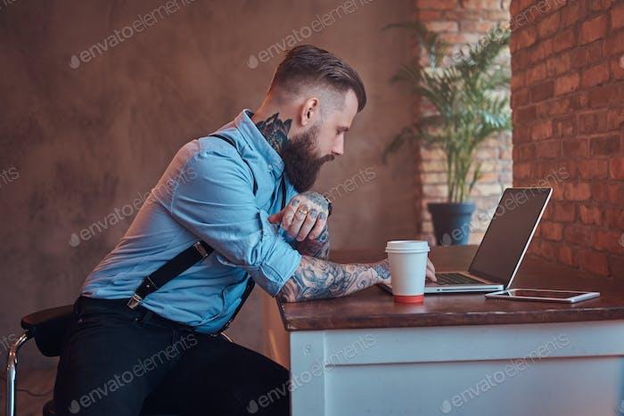 Красивый татуированный хипстер в кабинете с интерьером лофта.