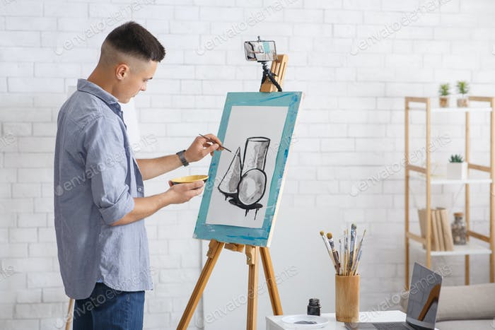 Home activity or leisure time during quarantine at home. Young guy drawing abstract picture