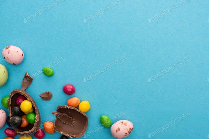 Stücke und die Hälfte der Schokolade Osterei mit Süßigkeiten und bunte Wachteleier auf blauem Hintergrund