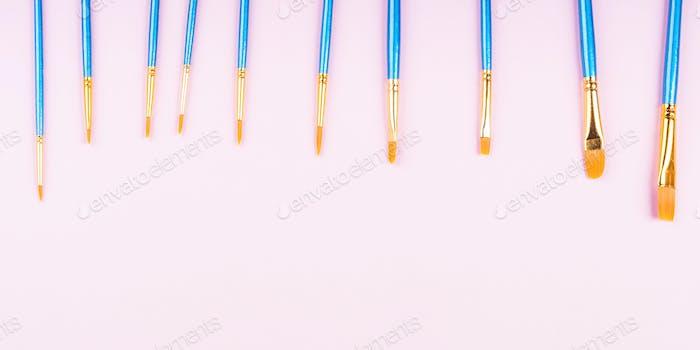 Blue paintbrushes on pink background