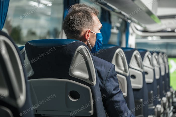 Male Passenger With Face Mask Sitting Inside Of Bus.