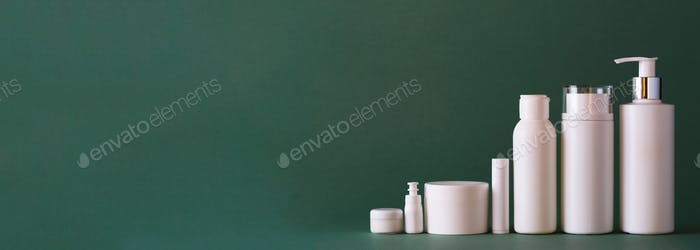 White cosmetic tubes on green background with copy space. Skin care, body treatment, beauty concept