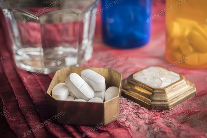 Metallic pillbox with white pills along with water glass