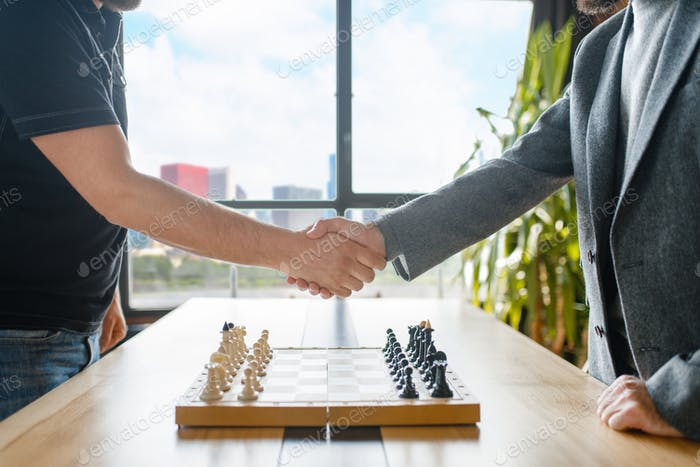 Male chess players shake hands before the game