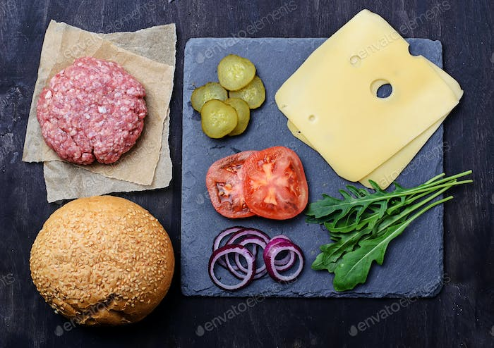 Ingredients for burger: raw cutlet, tomato, cheese, onion