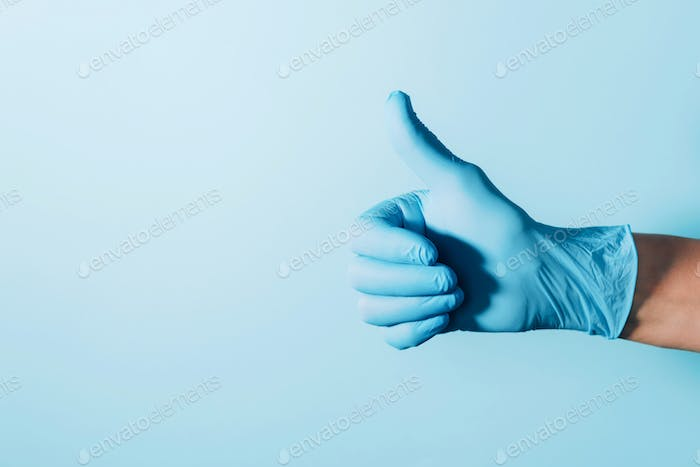 Doctor wears sterilized surgical gloves, thumb up on blue background. Copy space. National Doctors
