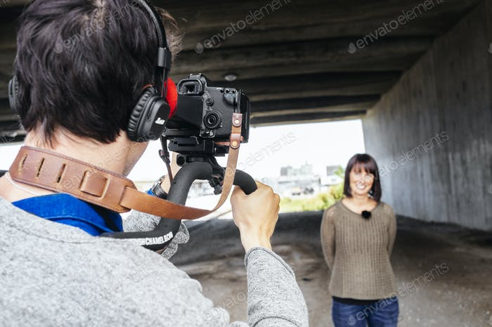 Cameraman filming news reporter under bridge
