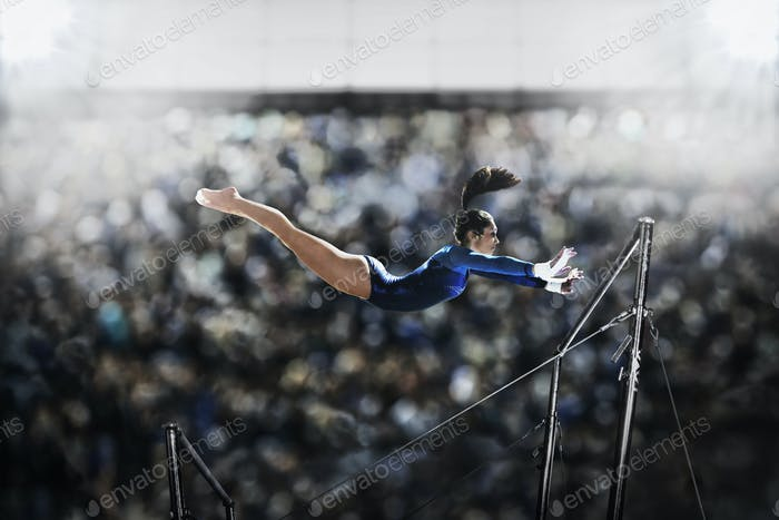A female gymnast in mid air reaching for the parallel bars.
