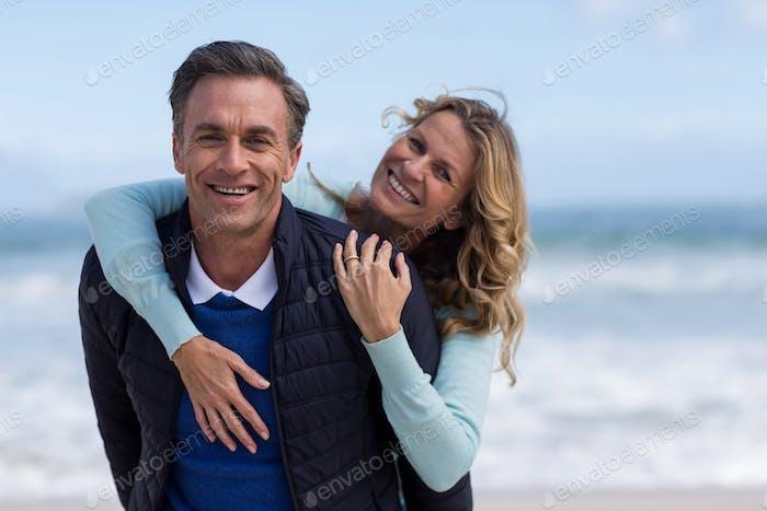 Mature man giving piggyback ride to woman on beach