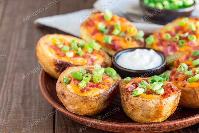 Baked loaded potato skins with cheddar cheese and bacon, garnish